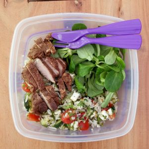 Spicy lamb, vegetarian rice salad and fresh green leaves for packed lunch