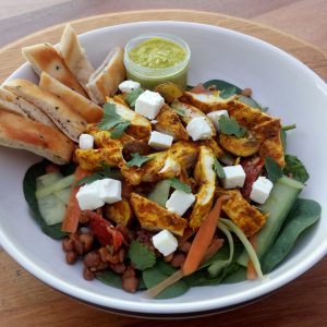 Chicken tikka salad with lentils, spinach, & naan bread